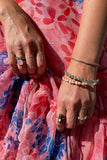Layered bangles and rings on pink floral dress