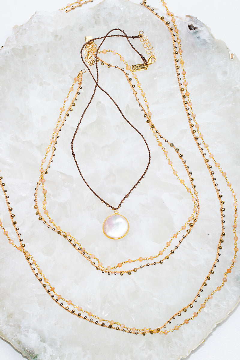 layered pearl and woven necklaces