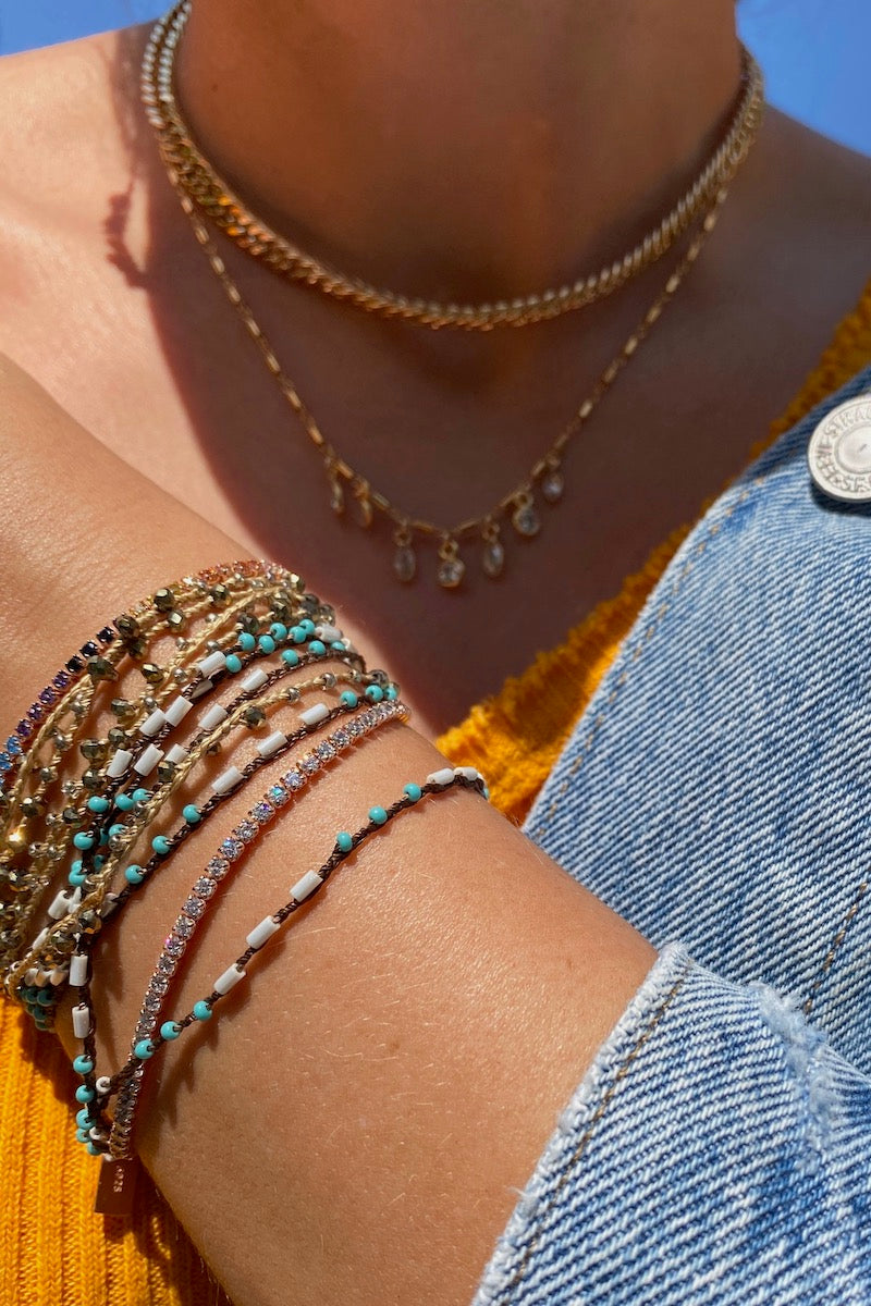 Mixed wrap bracelets and layered gold necklaces