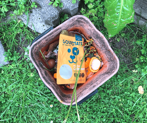 A Gourmate Pet Treat Co. Wild Caught Calamari packet sits in a bucket with other compostable food waste