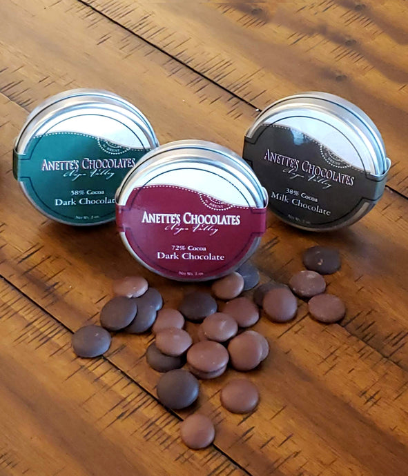 3 Tins displayed with chocolate disks in different cocoa percentages