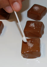 Load image into Gallery viewer, image of Himalayan salt being applied to salted Caramel piece