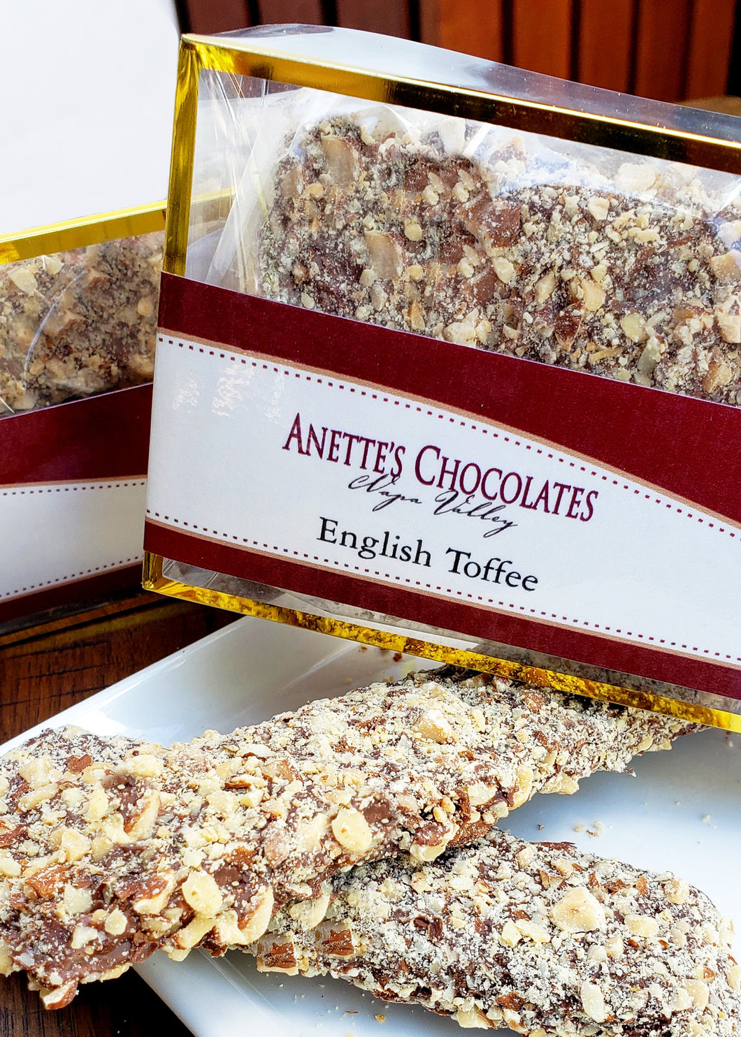 box of English toffee with pieces on a plate