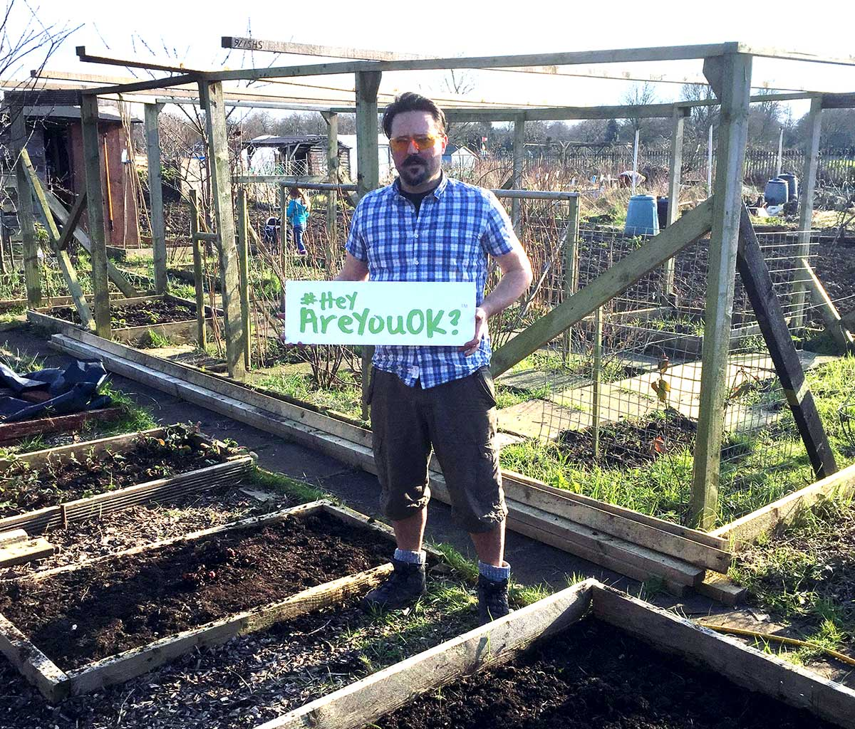Allotment Junkie holding a sign '#HeyAreYouOK' down the allotment plot showing support for the campaign