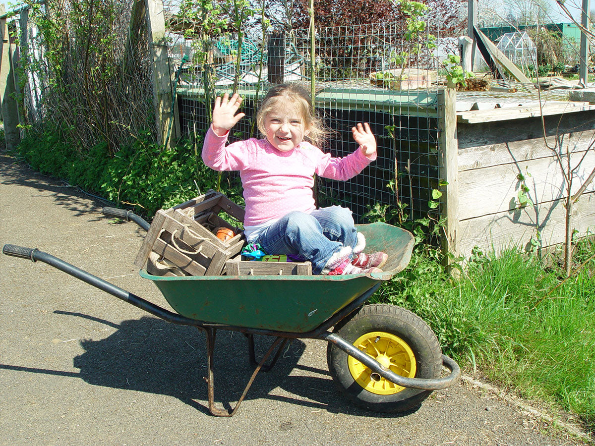 Little Yasmin sat the the wheelbarrow giving high fives on allotment junkies allotment plot