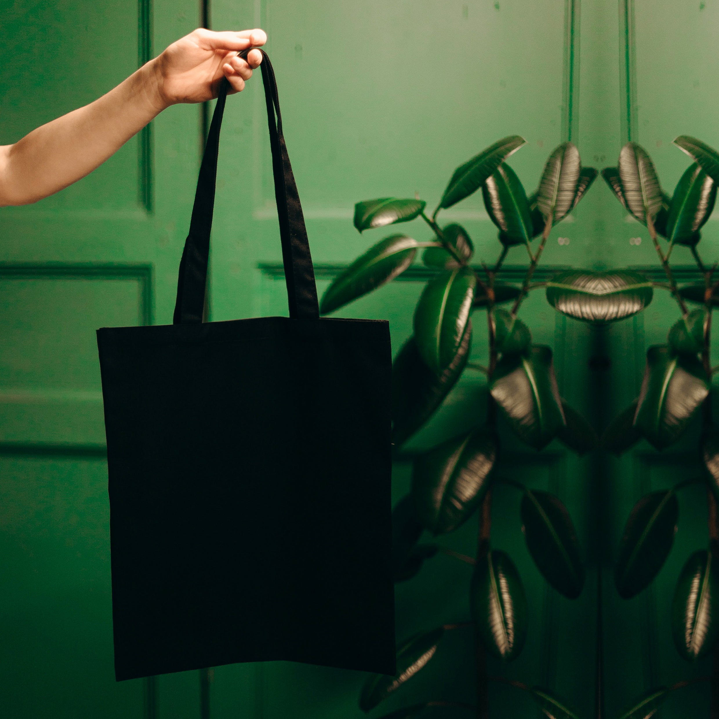 black tote bag with green background and plants
