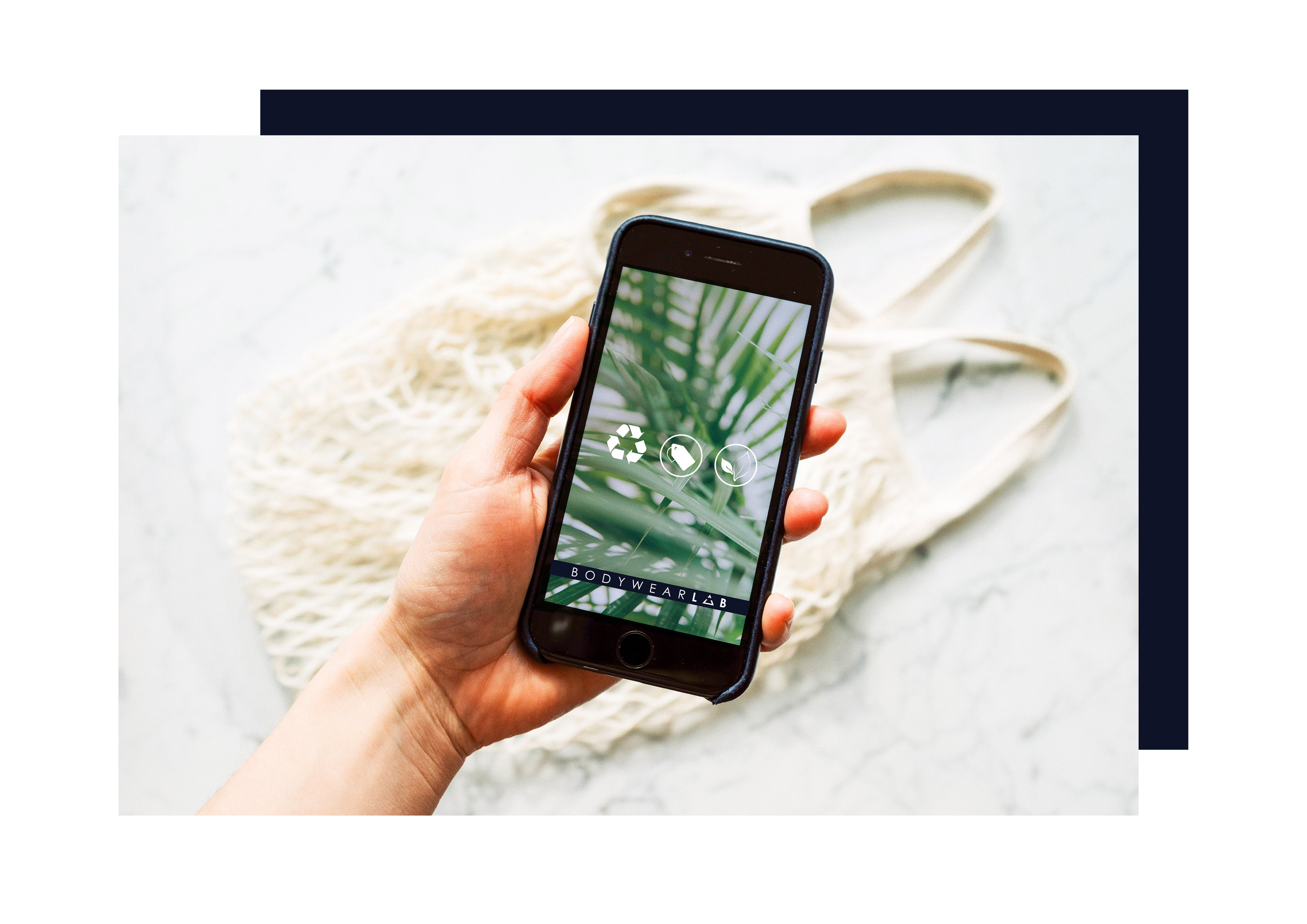 A mobile phone with a palm leaf and sustainable symbol background, in front of a sustainable shopping bag.
