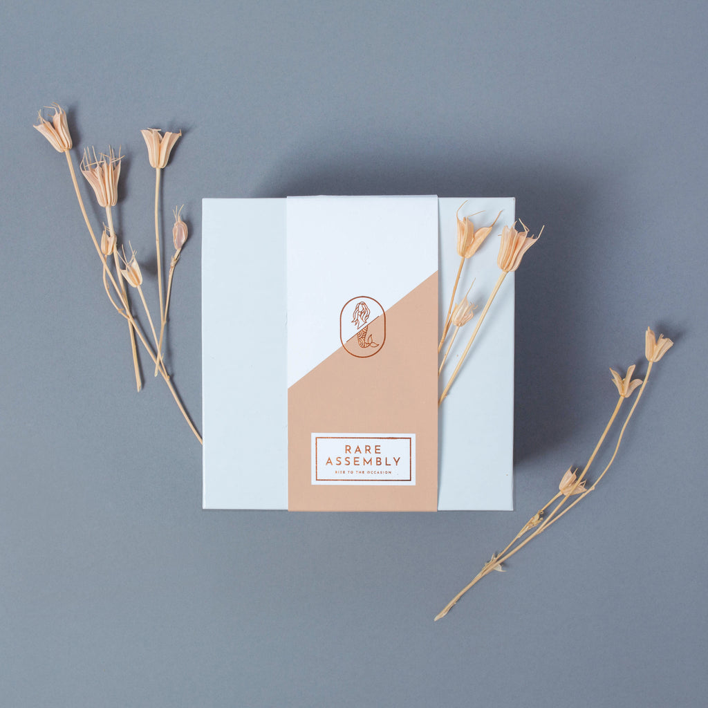 Modern gift box packaging details: coral belly band with copper hand stamped foil .