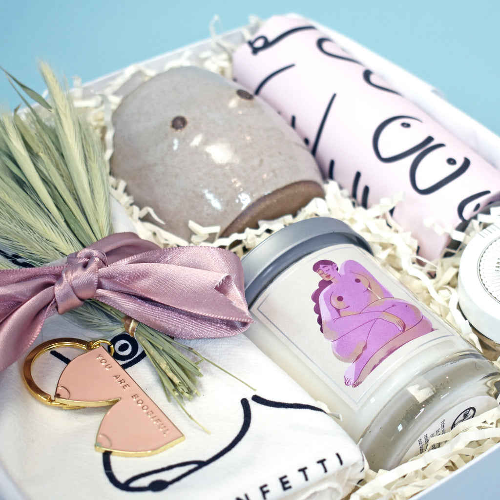 Modern gift box with boob theme: boob mug, naked lady candle, boob dish towel, tea in boob gift wrap, and champagne gummies. Perfect as a birthday gift, support gift, or friendship gift.