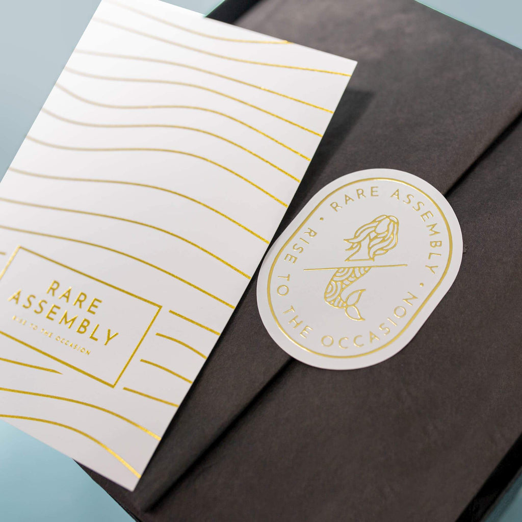 Black and gold holiday gift box packaging from Rare Assembly.