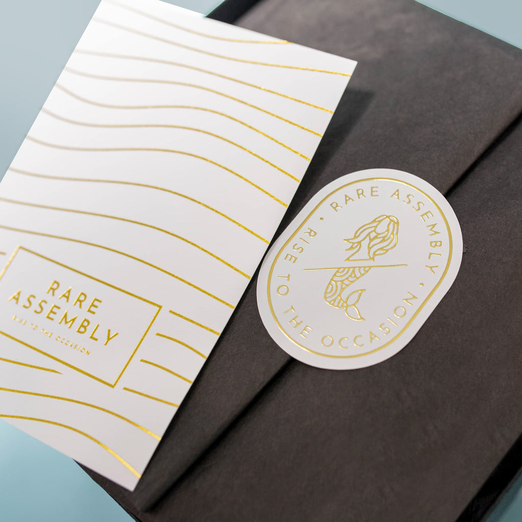 Modern gift box packaging from Rare Assembly in black + gold foil.