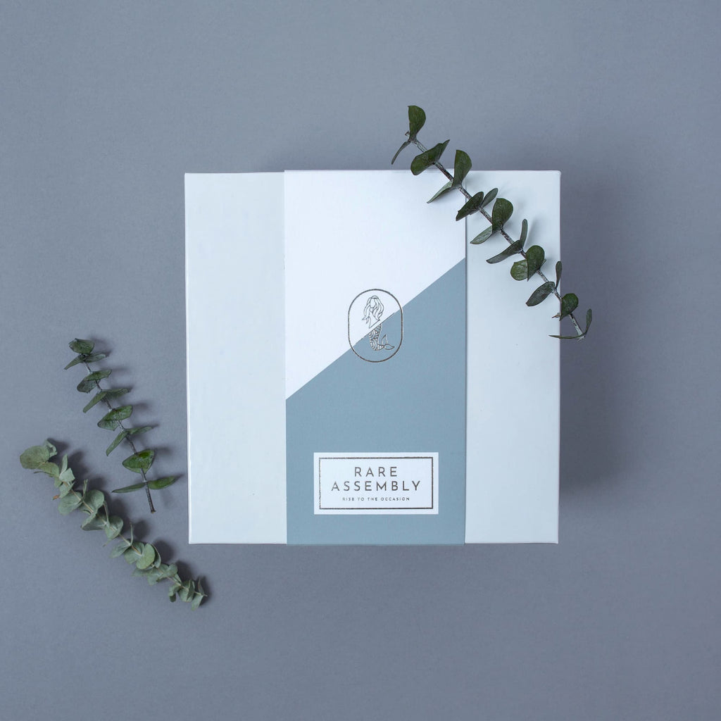 Modern gift box packaging from Rare Assembly in blue/grey with silver foil details.