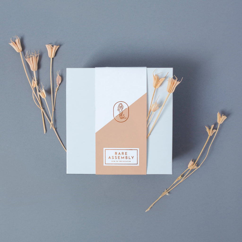 Modern gift box packaging design from Rare assembly in coral with copper foil.