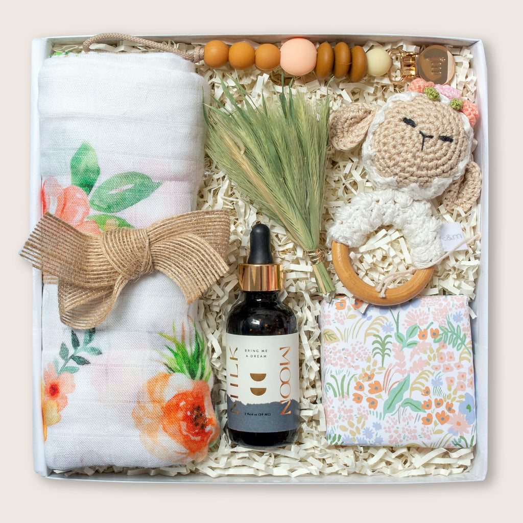 Modern gift box for new or expectant mom, new baby, or baby girl. Includes caramels, sleep tincture, lamb rattle, pacifier clip, and swaddle.