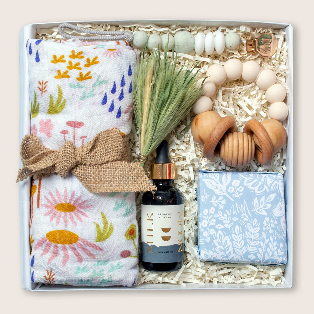 Modern gift box for baby boy, or gender neutral gift for new or expectant mom. Includes swaddle, caramels, rattle, pacifier clip and sleep tincture.