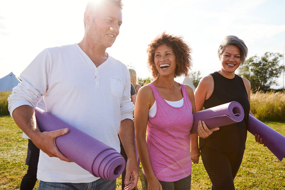 Mature Men And Women With Exercise Mats At End Of Outdoor Yoga Class