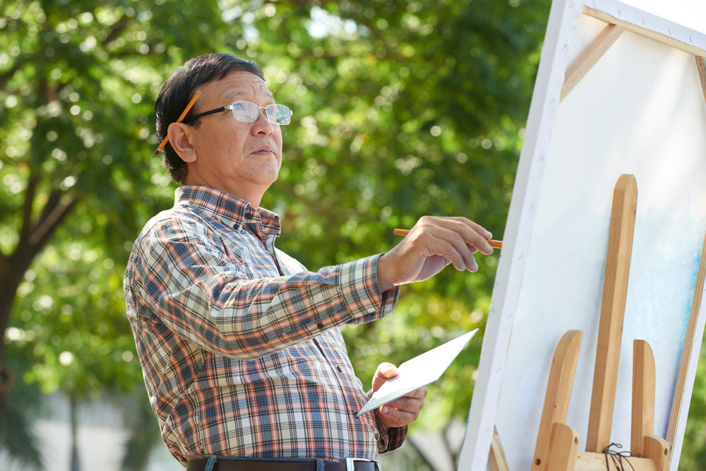 Middle-aged man painting outdoors.