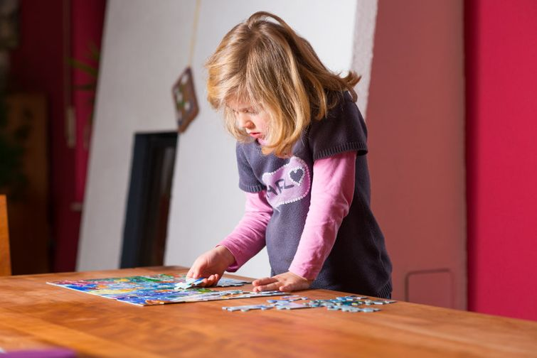 kid playing with jigsaw puzzle