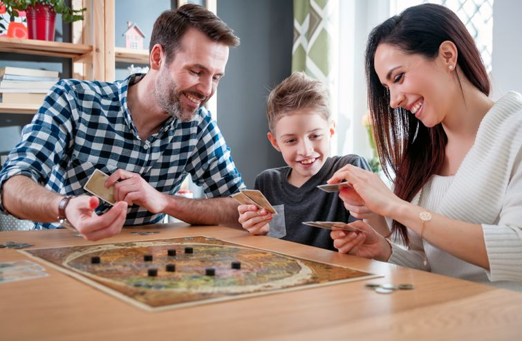 Happy family comparing cards from board game at living room table
