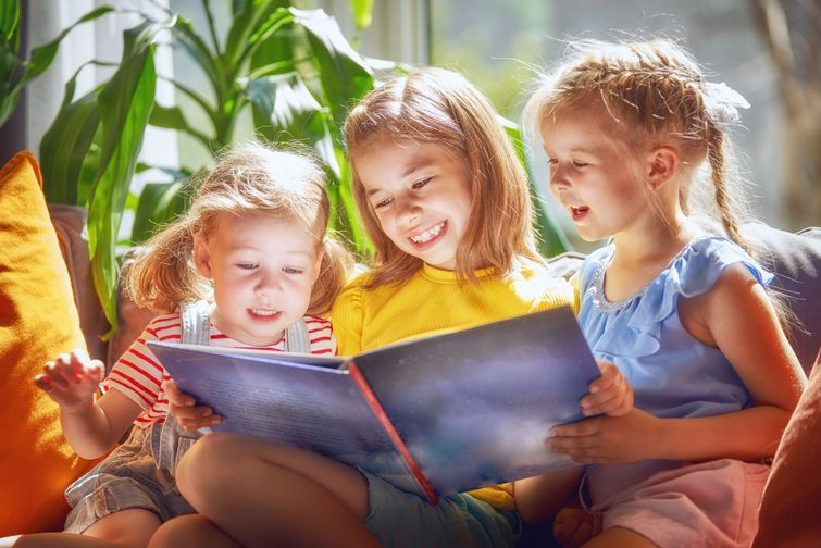 Three young girls flipping through recordable storybook together
