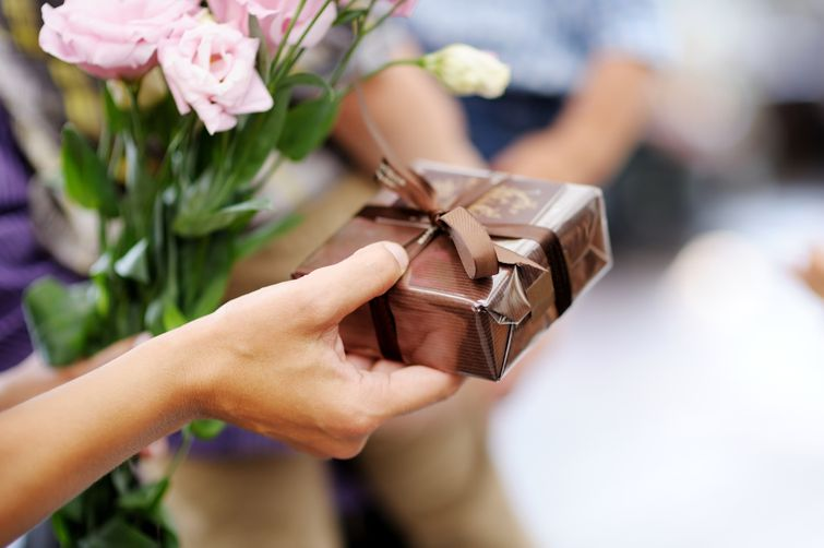 Timmins woman giving flowers and wrapped personalized gift to significant other