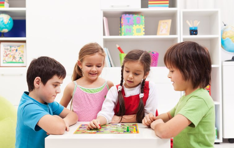 Four young kids playing board game at home