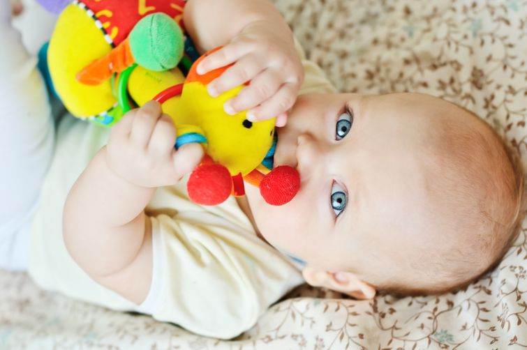 Baby chewing on cute giraffe-shaped teething toy
