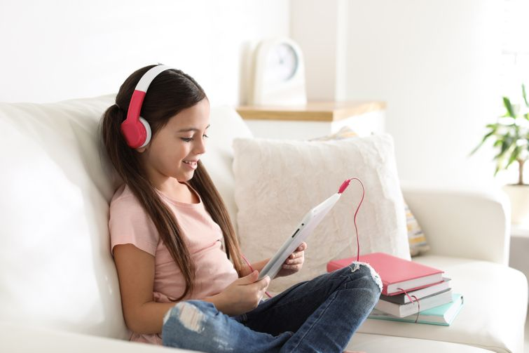 Young child with pink headphones listening to recordable storybook on tablet