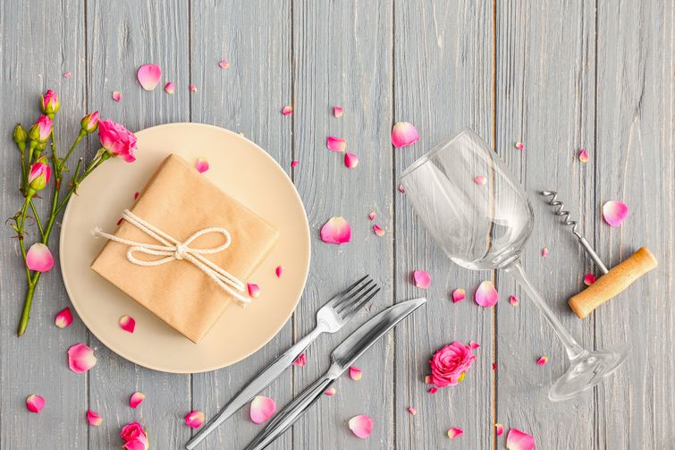 Table setting with personalized gift on plate, decorated with rose petals
