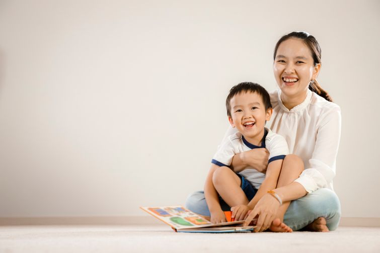 Young mother reading recordable storybook with laughing child