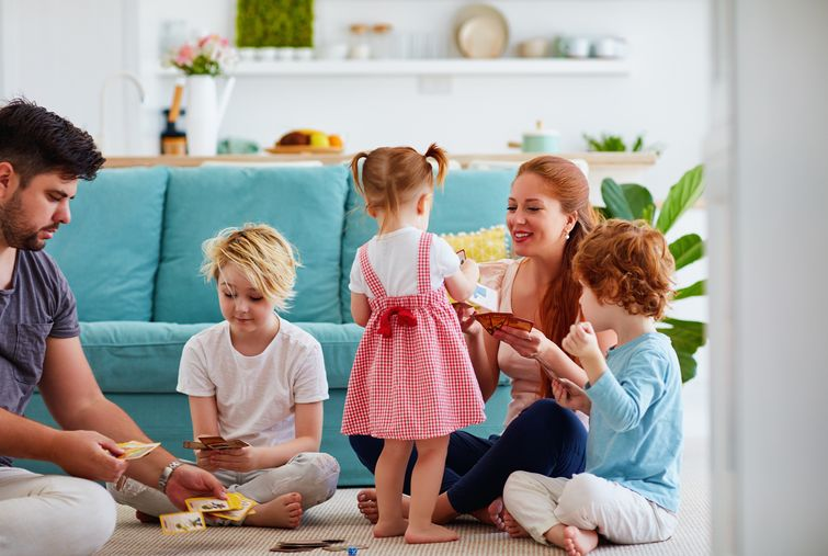 Happy family playing card game together on living room carpet