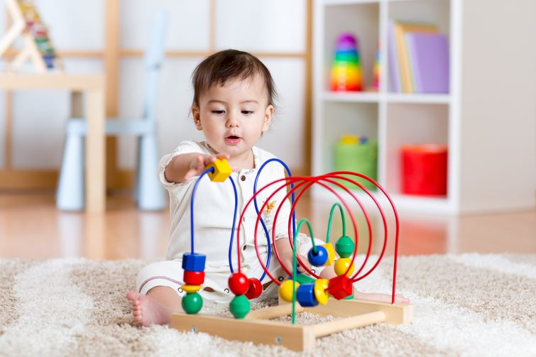 Infant boy playing with colourful baby playset in Timmins nursery