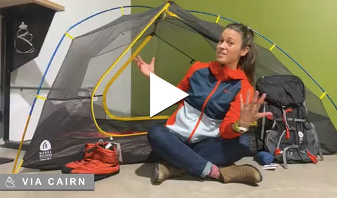 Woman sitting in front of camping gear