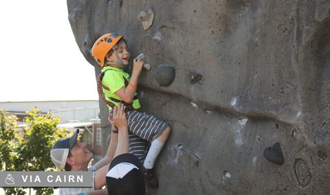 Young boy being helped up a climbing wall
