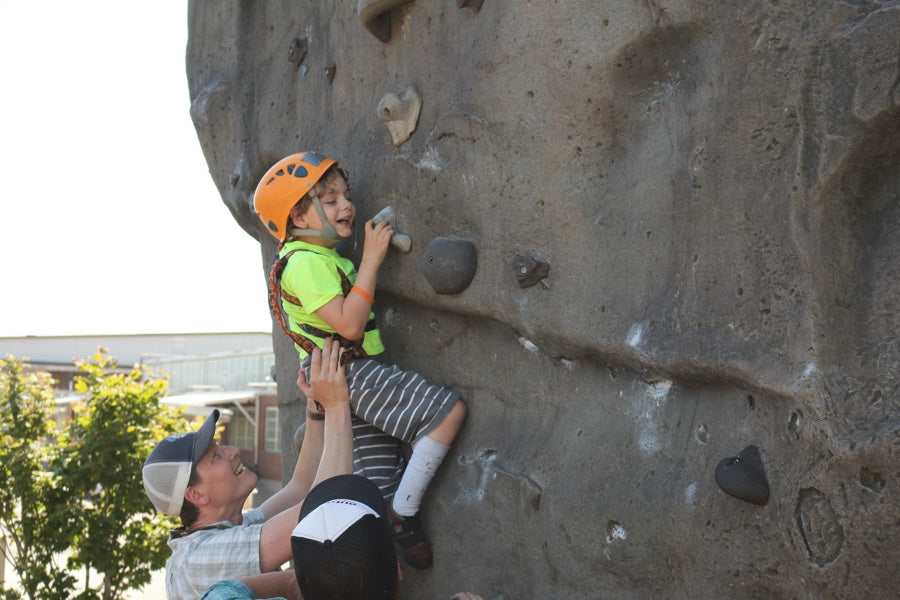 Young boy being helped on climbing wall