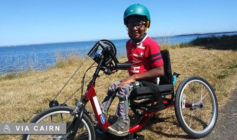Young disabled boy laughing and riding bike