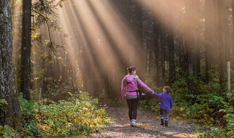 Woman and child walking in woods