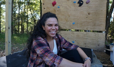 Woman sitting in front of climbing wall