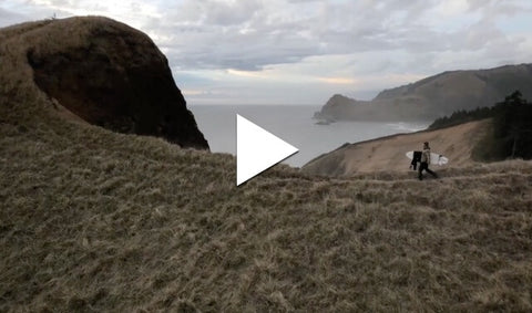Person walking along coastal cliff with surfboard