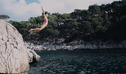 Kid jumping into a lake off of a rock