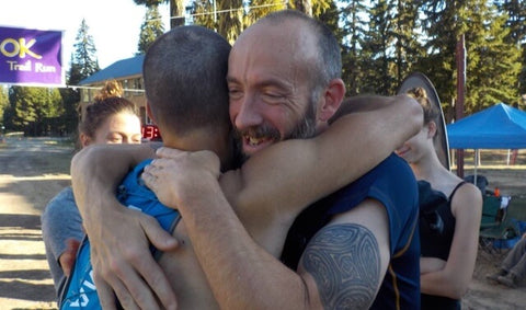 Two runners hugging