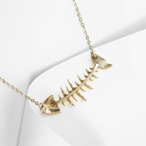A curvy golden fish bone, complete with glimmering crystal eye - centers this stylishly whimsical statement necklace.