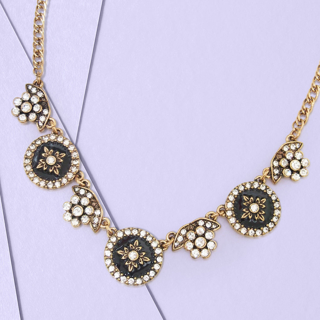 For a fashionista-approved addition to every it-girl's wardrobe, as a garland of floral motifs guides the eye to a burst of clear crystals in this statement-making collar. This necklace highlights floral shape charms embellished with crystals, and also features black enamel floral charms embellished with crystals, finished in antique and vintage tone zinc alloy. Day or night, you'll dazzle in this dramatic necklace.