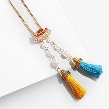 Load image into Gallery viewer, Show your unique style with this playful crystal encrusted and delicate chains of an elegant necklace finished with a pair of dainty tassels. This adjustable lariat pendant necklace is the perfect addition to any wardrobe all year long. Enjoy on-trend elegance with this delicate necklace in gold-tone finish.  It adds just the right amount of sparkle for any occasion. Use the special sliding closure to adjust the length of the necklace, from a choker to a longer style, and play with different effects.