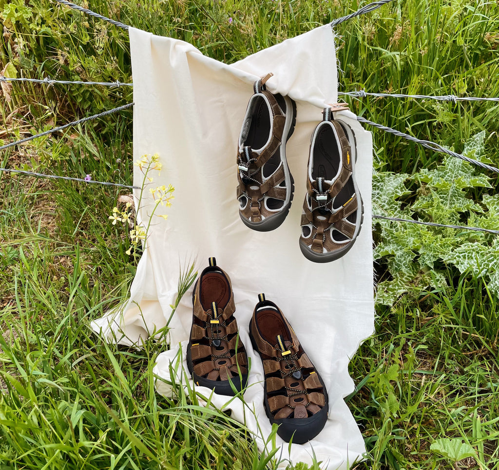 A pair of Keen Newports and Keen Venice Sandals on a white sheet in a field of grass