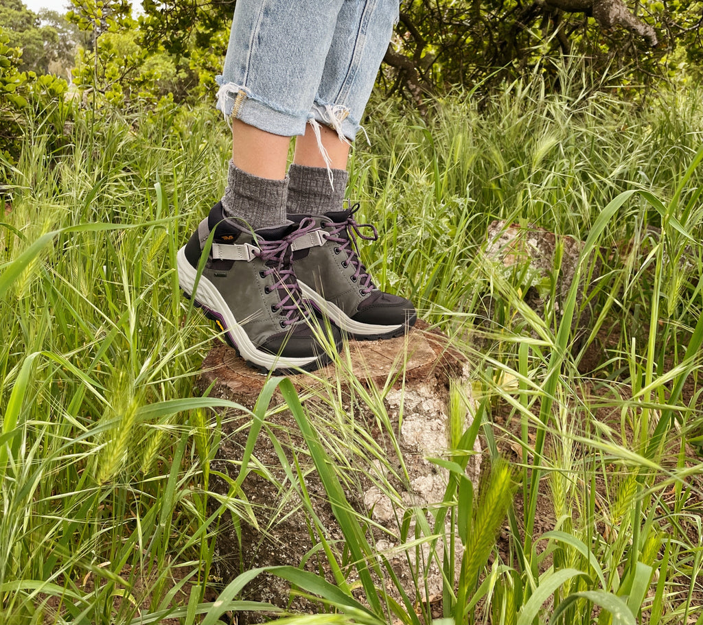 Picture from the knee down of someone standing on a log wearing Teva Grandview lace-up boots
