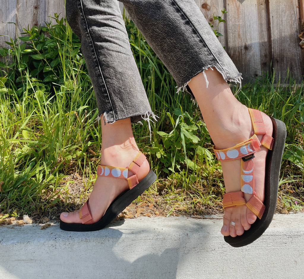 Person wearing rust colored Teva sandals with moon designs standing on a curb in front of grass and a fence