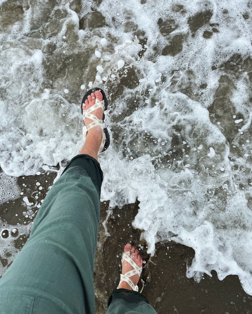 Photo looking down at feet wearing white Chaco sandals while walking into the ocean on the beach
