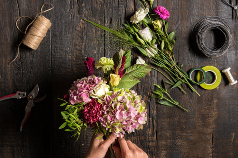 Florist with flowers, working tools and ribbon