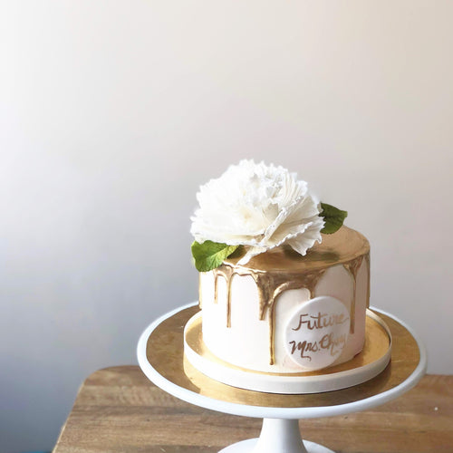 Photo of a white cake with gold ganache dripping down the sides, a white handmade peony on top with green leaves.